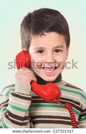 Adorable child speaking by a red phone isolated over green - stock photo