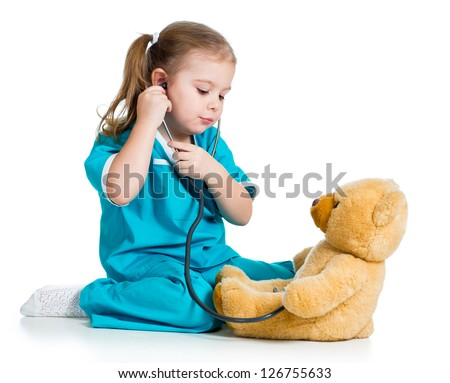 Adorable child with clothes of doctor playing and examining plush toy - stock photo