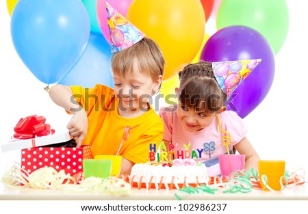 adorable children celebrating birthday party and opening gift box - stock photo
