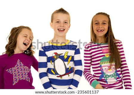 Adorable children laughing wearing colorful Christmas pajamas - stock photo