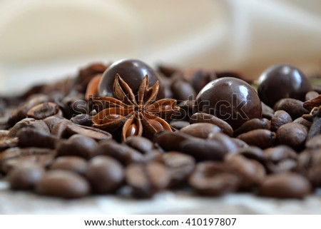 Adorable coffee beans background with small glitter chocolate balls and flavoring. - stock photo