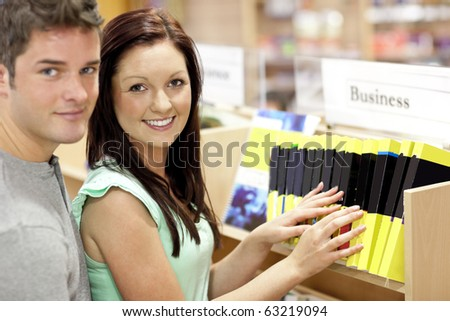 Adorable couple looking for a business book in a library smiling at the camera - stock photo