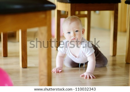 Adorable crawling baby girl under a table - stock photo