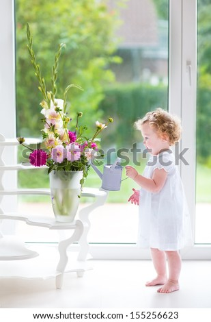 Adorable curly baby girl in a white dress watering flowers in a beautiful living room with a big window and door to the garden - stock photo