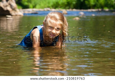 Adorable curly baby girl splashing in a beautiful river on a sunny summer day - stock photo