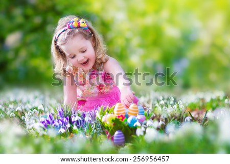 Adorable curly toddler girl in a pink summer dress playing with Easter eggs during egg hunt in a sunny garden with first white spring flowers  - stock photo