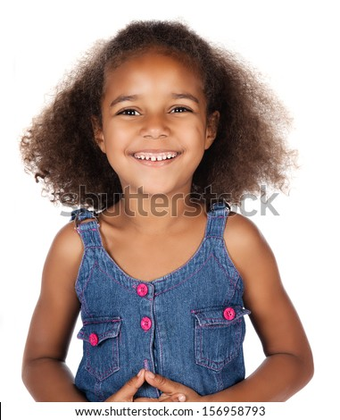 Adorable cute african child with afro hair wearing a denim dress. The girl is standing and smiling at the camera. - stock photo