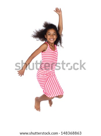 Adorable cute african child with afro hair wearing a white and pink striped dress. The girl is jumping and smiling. - stock photo