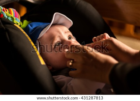 Adorable, cute baby portrait with big, brown, bright eyes, while resting in a pram on his christening festivity. - stock photo