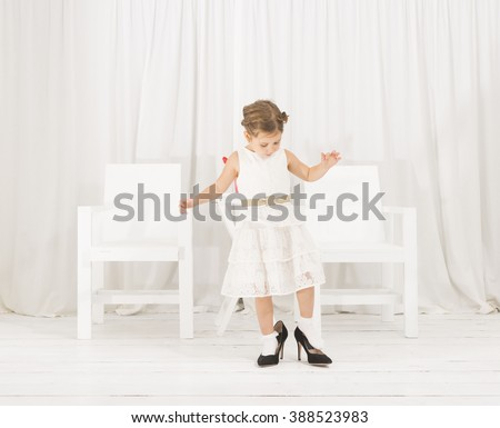 Adorable cute caucasian girl wearing white dress and black high heel shoes. Cute little girl trying to walk with big high heel shoes. Little girl fashionista in her mother's big heeled shoes - stock photo