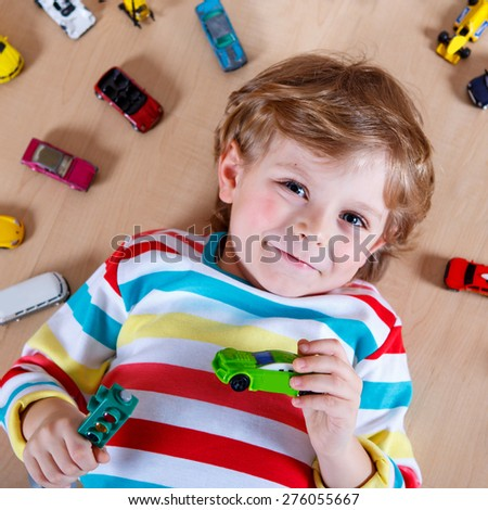 Adorable cute child with lot of different colorful toy cars. Happy boy playing with toys. - stock photo