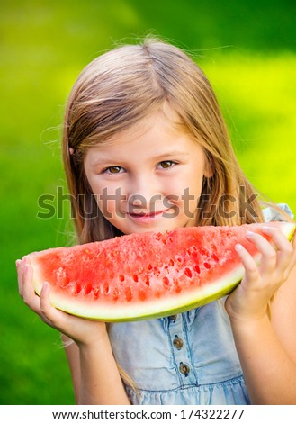 Adorable cute little girl eating watermelon on the grass in summertime - stock photo