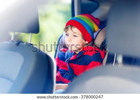 Adorable cute preschool kid boy sitting in car. Child in safety car seat with belt. Safe travel with kids and traffic laws concept. - stock photo