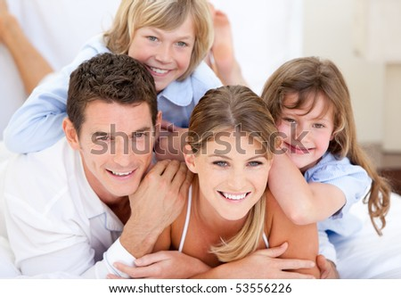 Adorable family looking together at the camera  in the bedroom - stock photo