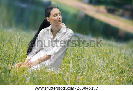 Adorable female with closed eyes relaxing on meadow, outsides. Young beautiful girl in a grass - stock photo