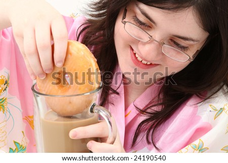 Adorable fifteen year old girl dunking her doughnut into her coffee. - stock photo
