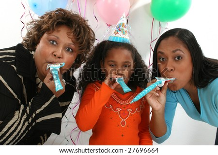 Adorable five year old African American Girl celebrating birthday with mother and grandmother. - stock photo