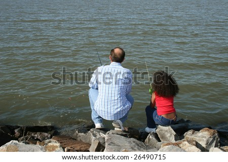 Adorable five year old African American Girl fishing with her father. Multi racial family. - stock photo