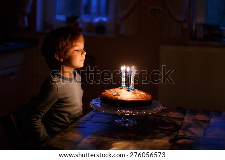 Adorable five year old kid celebrating his birthday and blowing candles on homemade baked cake, indoor. Birthday party for children. - stock photo