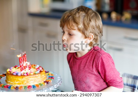 Adorable four year old kid boy celebrating his birthday and blowing candles on homemade baked cake, indoor. Birthday party for kids. - stock photo