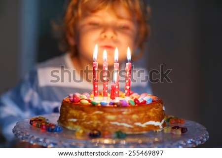 Adorable four year old kid celebrating his birthday and blowing candles on homemade baked cake, indoor. Birthday party for kids. Focus on child - stock photo