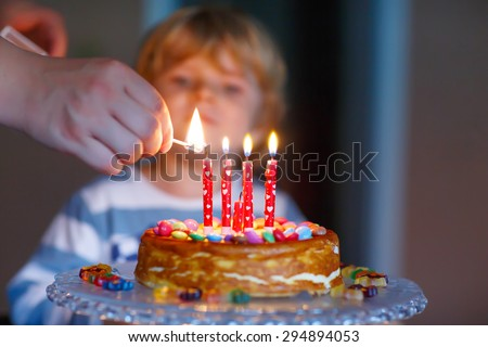 Adorable four year old kid celebrating his birthday and blowing candles on homemade baked cake, indoor. Birthday party for kids. Hand of adult with match - stock photo