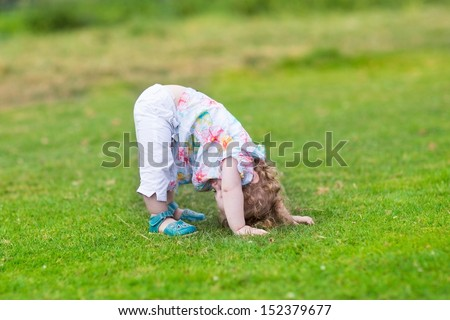 Adorable funny baby girl standing with her head down in a summer - stock photo