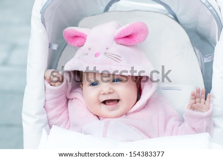 Adorable funny baby girl wearing a pink warm bunny snow suit sitting in a white stroller on a walk in a winter park - stock photo
