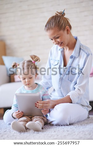 Adorable girl and her mother using digital tablet - stock photo