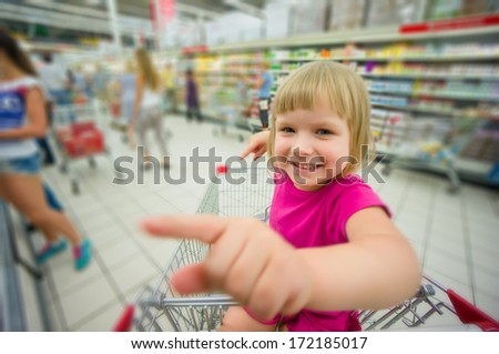 Adorable girl at shopping cart select products in supermarket - stock photo