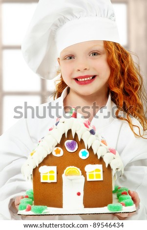 Adorable girl child in chef uniform holding a ginger bread, gingerbread house over white background. - stock photo