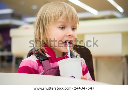 Adorable girl drink soda in fast food restaurant - stock photo