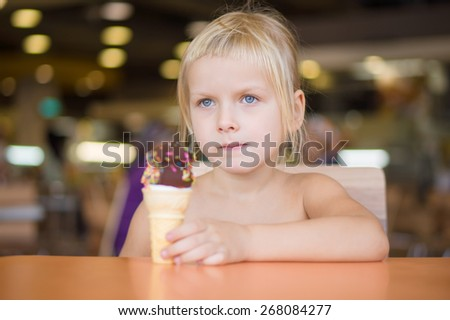 Adorable girl eat chocolate ice cream with sprinkles in mall - stock photo