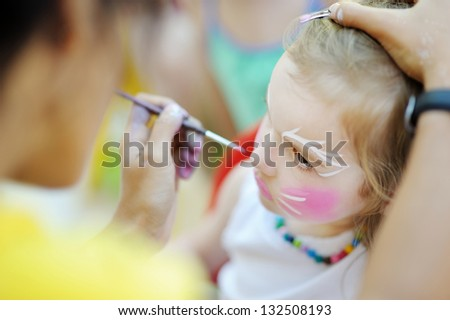 Adorable girl getting her face painted - stock photo
