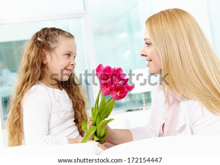 Adorable girl giving beautiful tulips to her mother - stock photo