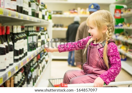 Adorable girl grimacing sitting in shopping cart in alcoholic beverages department in supermarket - stock photo