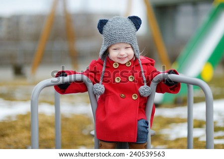 Adorable girl having fun on a playground on beautiful spring day - stock photo