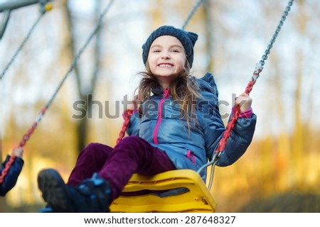 Adorable girl having fun on a swing on beautiful autumn day - stock photo
