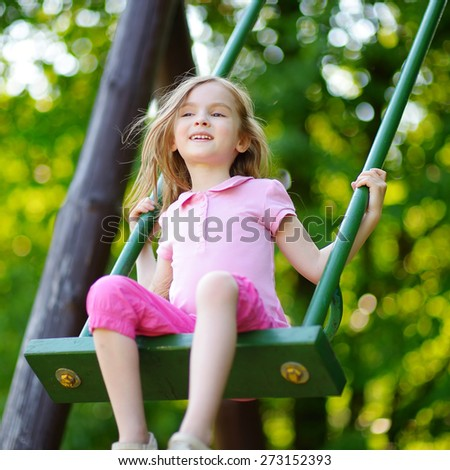 Adorable girl having fun on a swing on summer day - stock photo