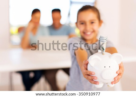 adorable girl holding piggybank with dollar banknotes - stock photo