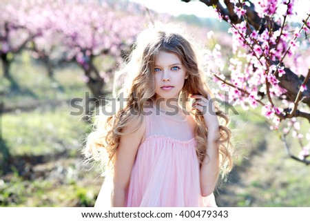 Adorable girl in blooming peach garden on  sunny spring day - stock photo