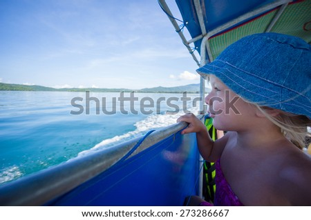 Adorable girl in blue hat on longtail boat in open ocean near islands - stock photo