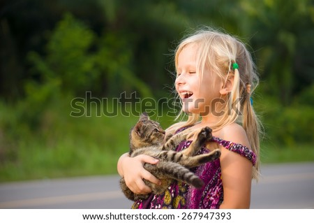 Adorable girl in color dress hold small kitten in hands - stock photo