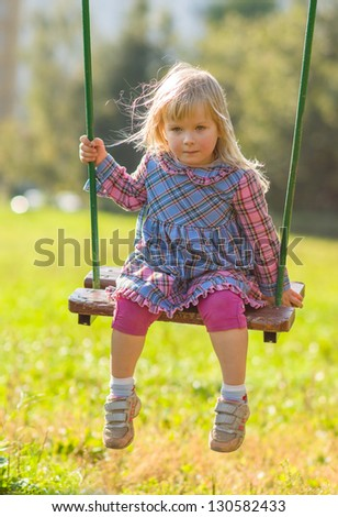Adorable girl in dress swing on playground in park - stock photo