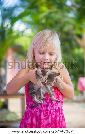 Adorable girl in pink color dress holds small kittens in hands - stock photo