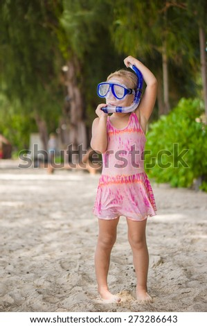 Adorable girl in pink swimming suit on the beach in snorkeling mask - stock photo