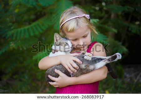 Adorable girl in red dress hold nice cat on hands - stock photo