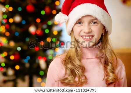 Adorable girl in Santa hat looking at camera with smile - stock photo