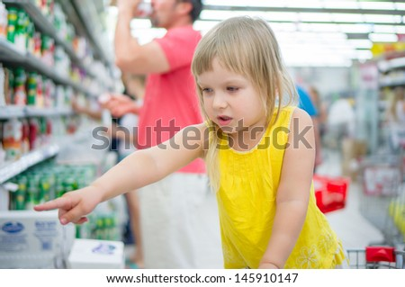 Adorable girl in shopping cart pointing hand to goods in supermarket - stock photo