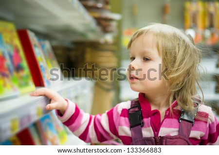 Adorable girl in shopping cart select books on shelves in supermarket - stock photo